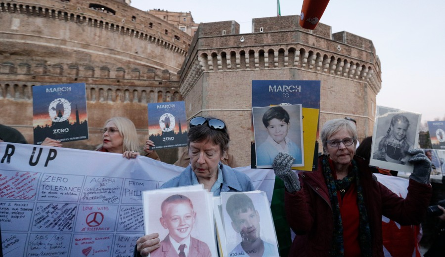 People hold up pictures of what they claim to be victims of priests sexual abuse as they gather during a twilight vigil prayer near Castle Sant' Angelo, in Rome, Thursday, Feb. 21, 2019. Pope Francis opened a landmark sex abuse prevention summit Thursday by warning senior Catholic figures that the faithful are demanding concrete action against predator priests and not just words of condemnation. (AP Photo/Gregorio Borgia) Vatican Sex Abuse