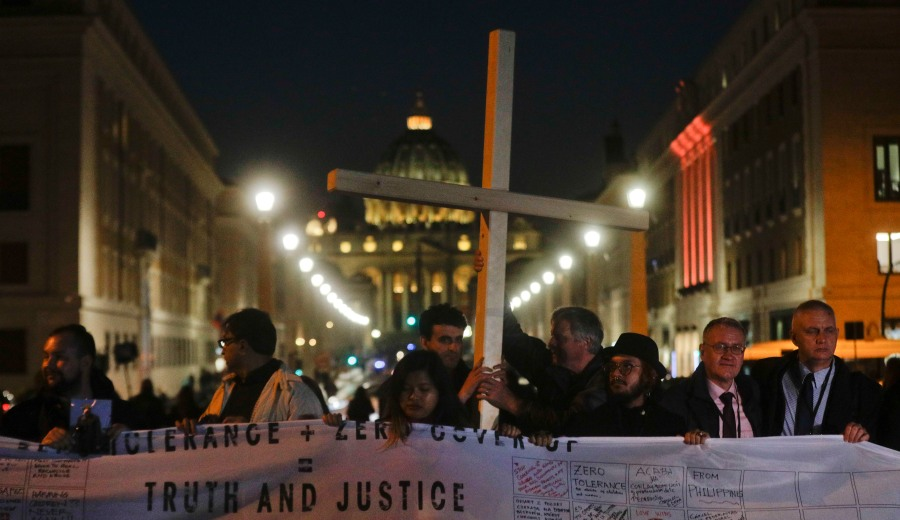 Survivors of sex abuse hold a cross as they gather in front of Via della Conciliazione, the road leading to St. Peter's Square, visible in background, during a twilight vigil prayer of the victims of sex abuse, in Rome, Thursday, Feb. 21, 2019 during a twilight vigil prayer near Castle Sant' Angelo, in Rome, Thursday, Feb. 21, 2019. Pope Francis opened a landmark sex abuse prevention summit Thursday by warning senior Catholic figures that the faithful are demanding concrete action against predator priests and not just words of condemnation. (AP Photo/Gregorio Borgia) Vatican Sex Abuse