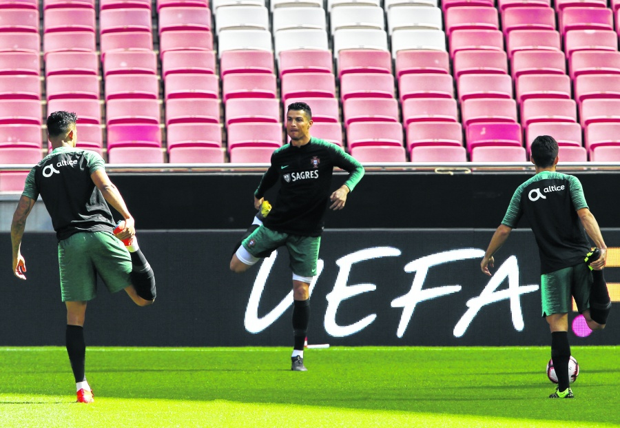Portugal's Cristiano Ronaldo, center, exercises during a training session of the Portuguese soccer team at the Luz stadium in Lisbon, Thursday, March 21, 2019. Portugal will play Ukraine in a Euro 2020 qualifying match March 22. (AP Photo/Armando Franca)