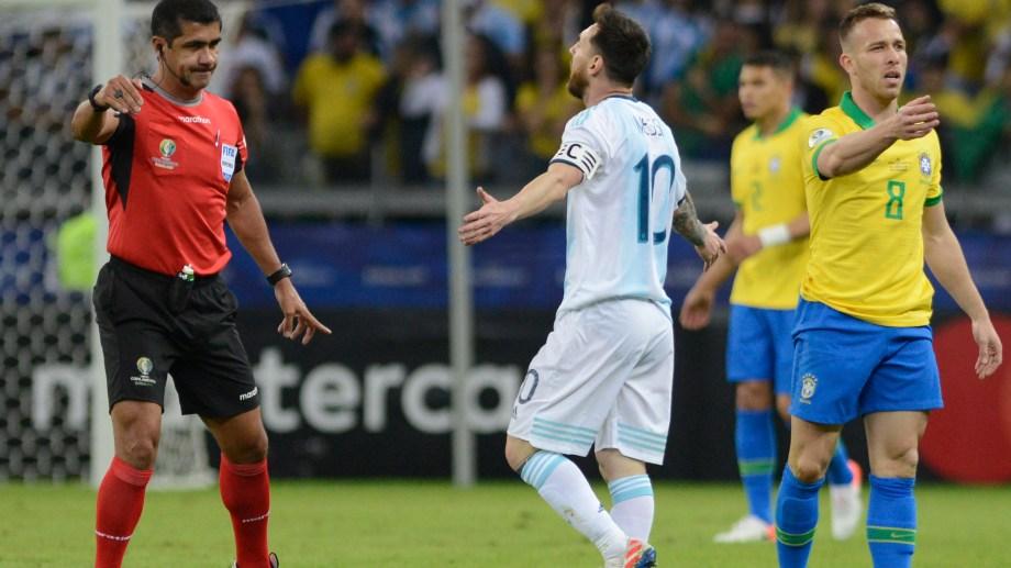 Lionel Messi se queja con el árbitro ecuatoriano Roddy Zambrano durante la semifinal ante Brasil en la Copa América en Belo Horizonte (AP Foto/Eugenio Savio)