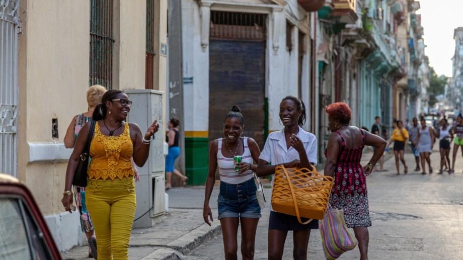 Una típica escena de La Habana, Tres empleadas salen de sus trabajos, a pura sonrisa.
