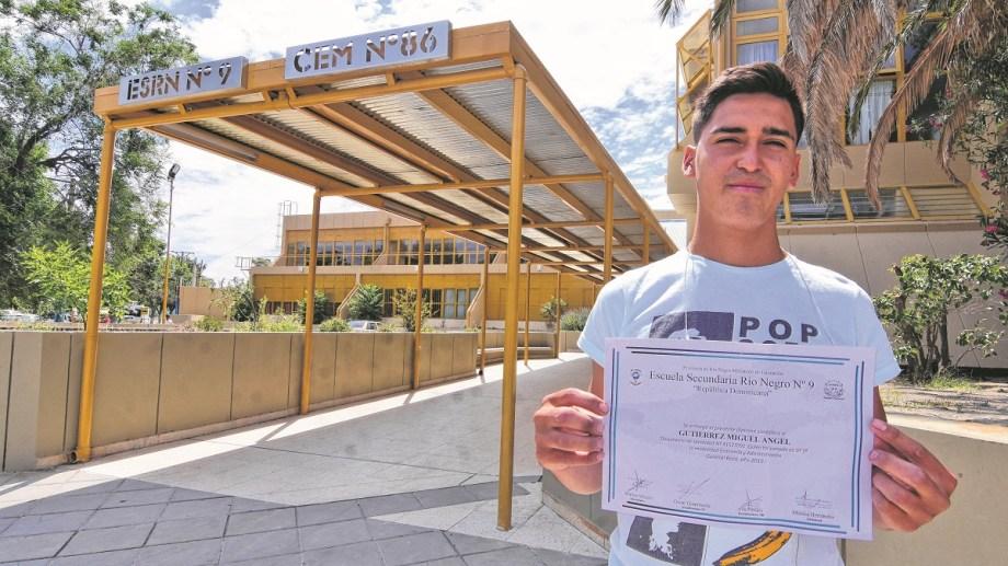 Miguel Angel Gutierrez, con diploma en mano en la fachada de su colegio, la ESRN N° 9.