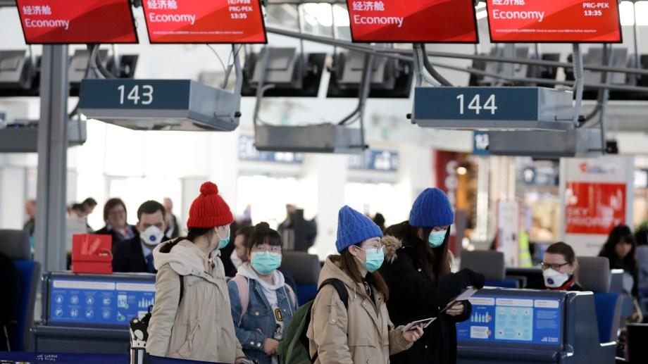 En el check in de un vuelo en Beijing, las máscaras también son protagonistas. (Foto AP)
