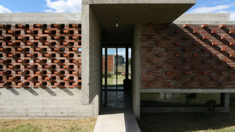 Un corte neto en la continuidad ladrillera de la fachada señala el ingreso.