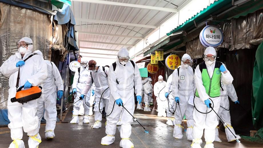 En Corea, trabajadores usan protección para desinfectar la zona de un mercado, de manera preventiva. Foto AP.