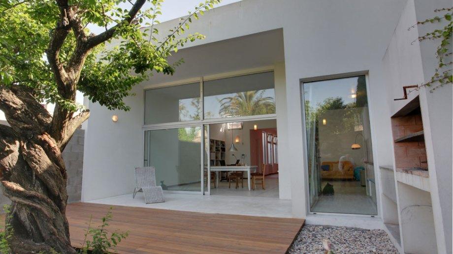 El living, comedor, cocina y bibliotecta -un gran ambiente único- dan al contrafrente, abierto al patio trasero con un hermoso y añejo árbol.