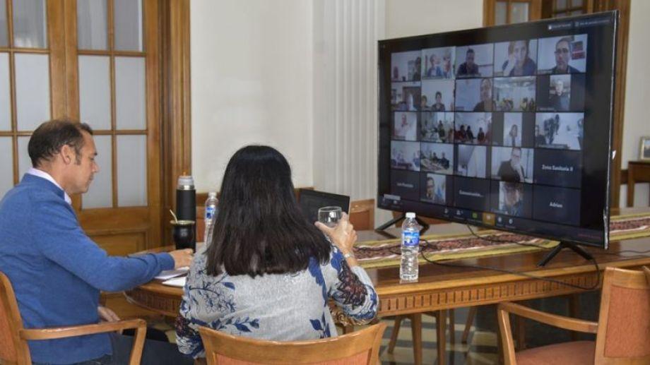 El gobernador Omar Gutiérrez y la ministra Andrea Peve (de espaldas) mantuvieron un encuentro virtual con integrantes del sistema de salud. Foto Neuquén Informa