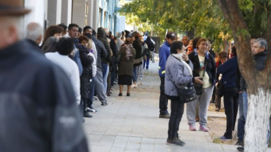 Cientos de vecinos esperan desde la madrugada ser atendidos en la sucursal del banco Nación, en Roca. (foto y video Juan Thomes)
