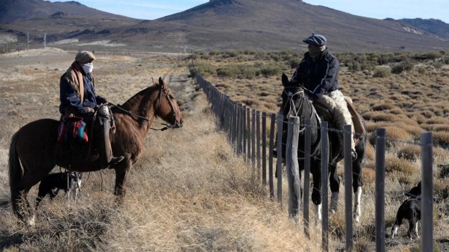 Francisco Antonio Moya (a la izquierda) y César Cornejo en plena charla en el medio del campo, a unos 64 kilómetros de Bariloche. (foto Alfredo Leiva)