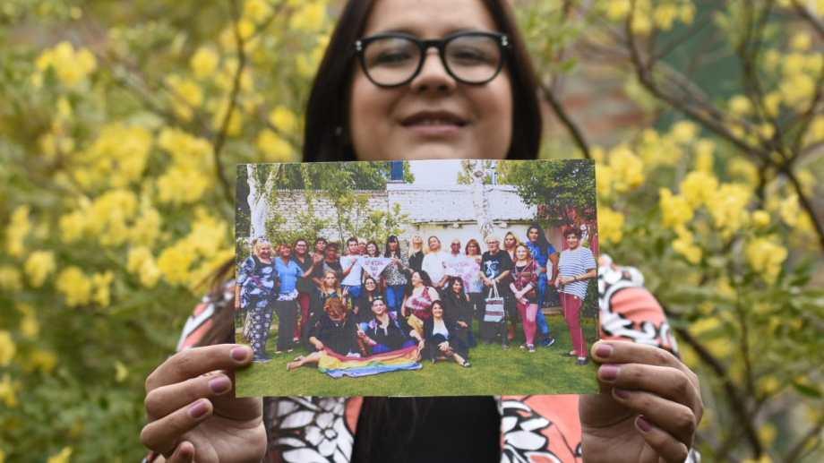 """Tatiana sostiene una foto en la que aparecen todas sus compañeras. Dice que es una de sus favoritas porque están """"todas sonriendo."""" Foto Florencia Salto."""