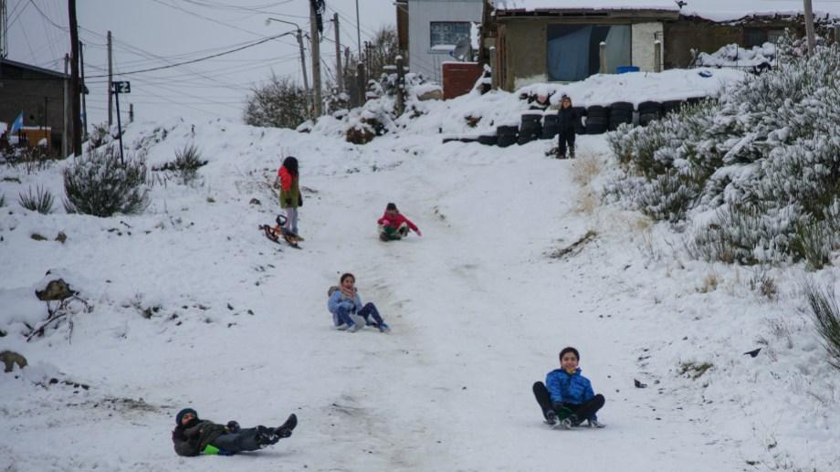Niñas y niños de los barrios del Alto de Bariloche se divierten en la nieve tras semanas de cuarentena por el coronavirus. Foto: Marcelo Martínez