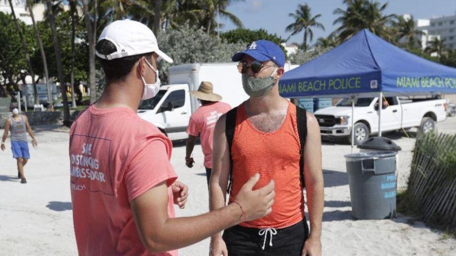 Los embajadores de la ciudad reciben a los visitantes y les recuerdan que deben usar barbijos al ingresar y respetar la distancia. Foto: Wilfredo Lee / AP