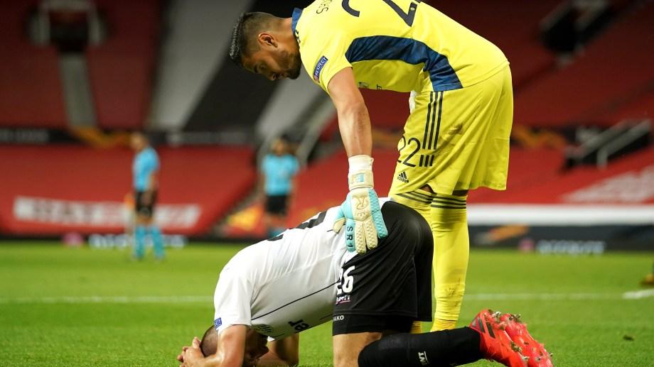 Chiquito Romero consuela a Reinhold Ranftl, del Copenaghe. El arquero argentino fue titular en el Manchester United, que está en las semifinales. (AP Photo/Dave Thompson)