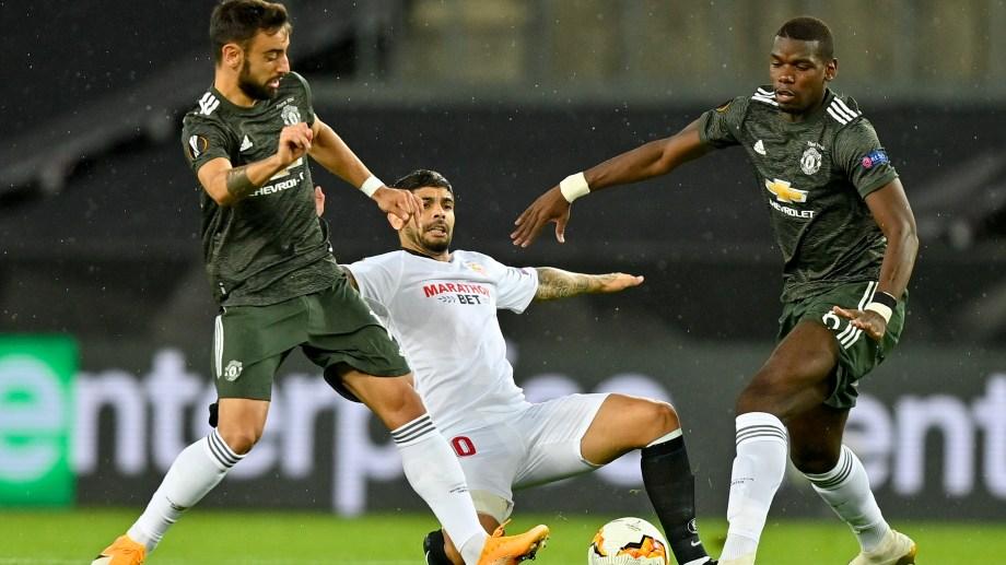 Banega pelea por el balón entre Bruno Fernandes y Pogba. El Sevilla ira el viernes por su sexta Europa League. (AP Photo/Martin Meissner, Pool)