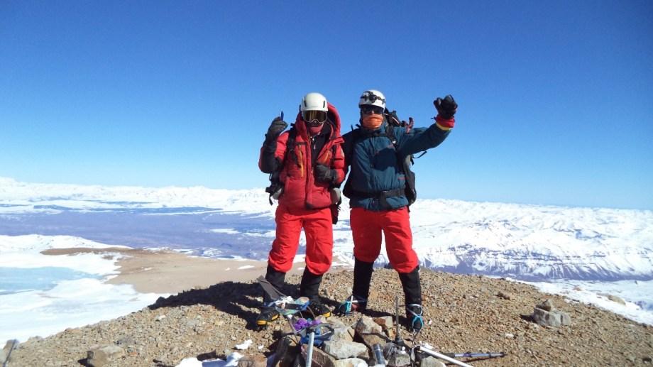 Momento cumbre. Daniel Castillo y Héctor Valdez saludan a la cámara de Damián Hernández en la cima del volcán Domuyo, el punto más alto de la Patagonia.,