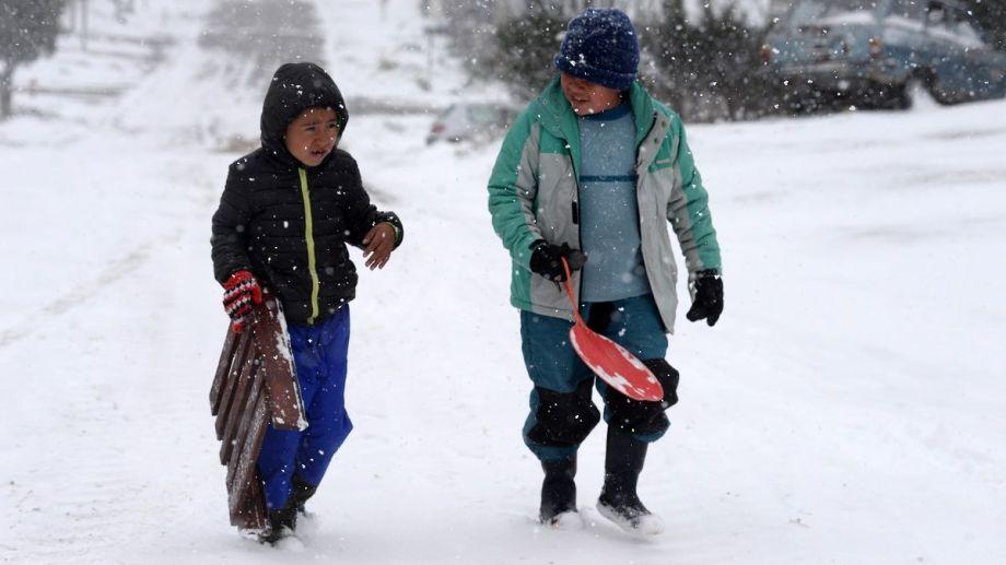 Los chicos aprovechan la nieve de octubre para tirarse con trineos en calles con pendientes de los barrios de Bariloche. Foto: Alfredo Leiva