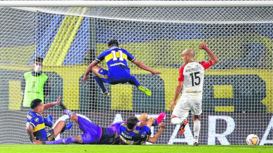 Carlitos Tevez se anticipa a Soldano y a Salvio para marcar el segundo gol de Boca ante el Caracas. El Apache fue una de las figuras. (Foto/AP)