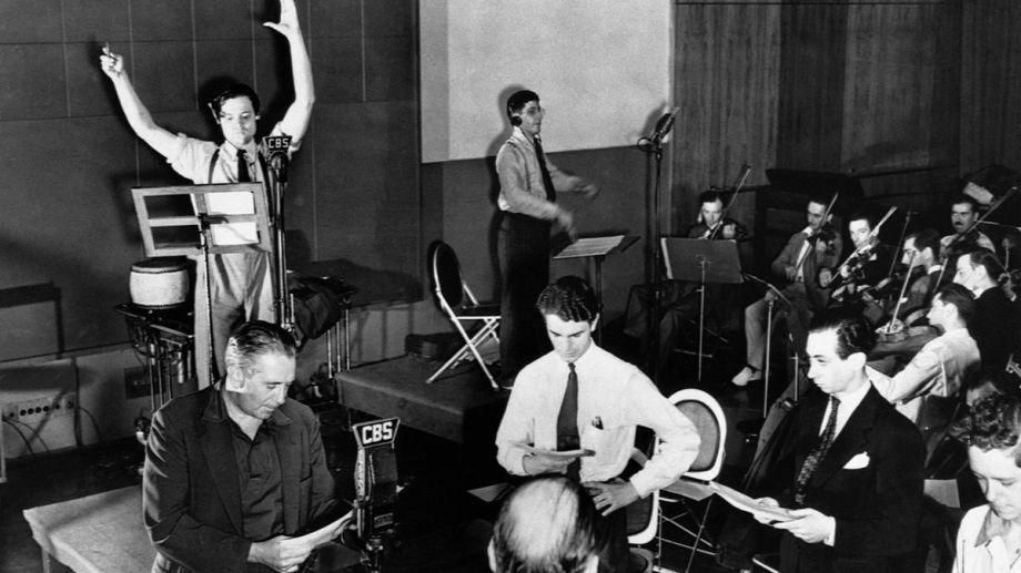 """Orson Welles, con los brazos en alto, en plena emisión de """"La Guerra de los Mundos"""" en los estudios de la CBS."""