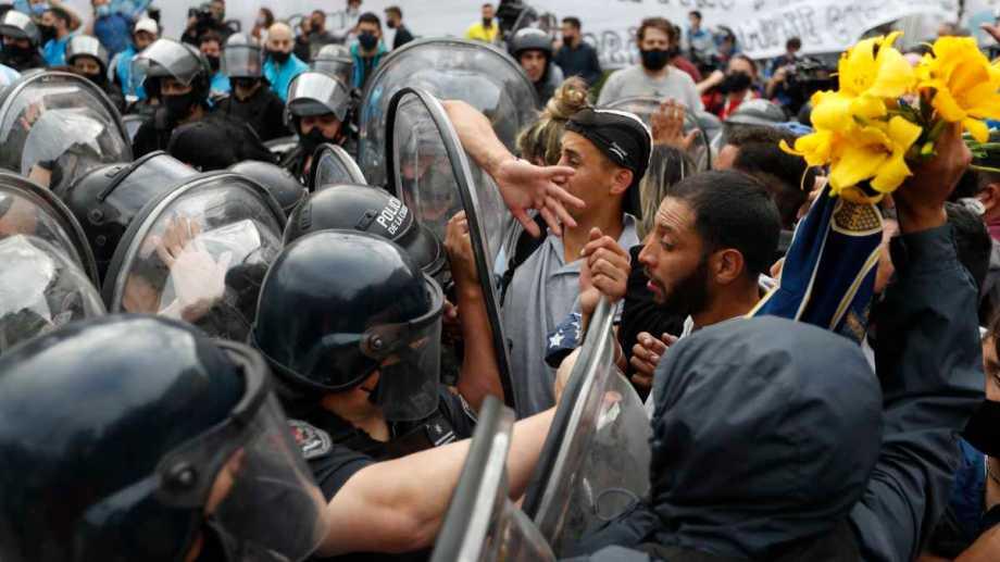 Fanáticos que esperaban en la fila para despedir a Diego Maradona se enfrentan con la policía. Foto: Natacha Pisarenko (AP)