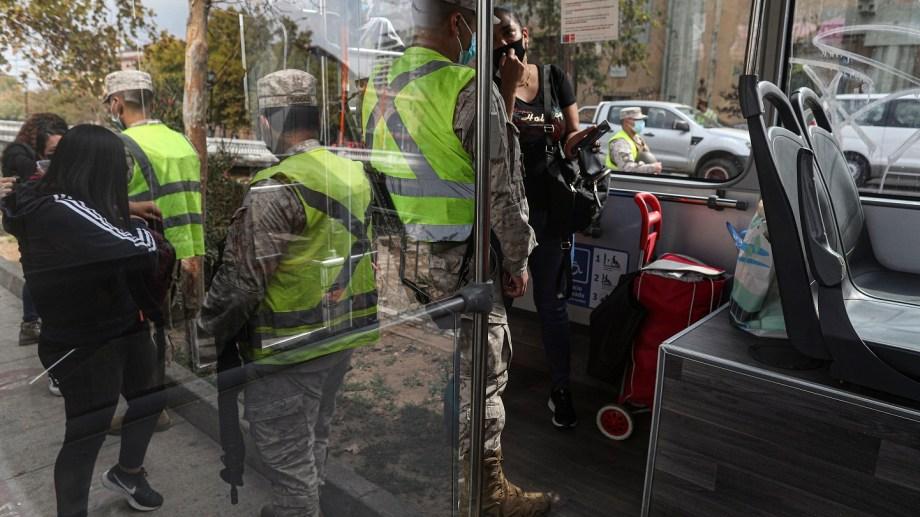 Soldados chequean los permisos de circulación de transeúntes en Santiago (AP Photo/Esteban Felix)