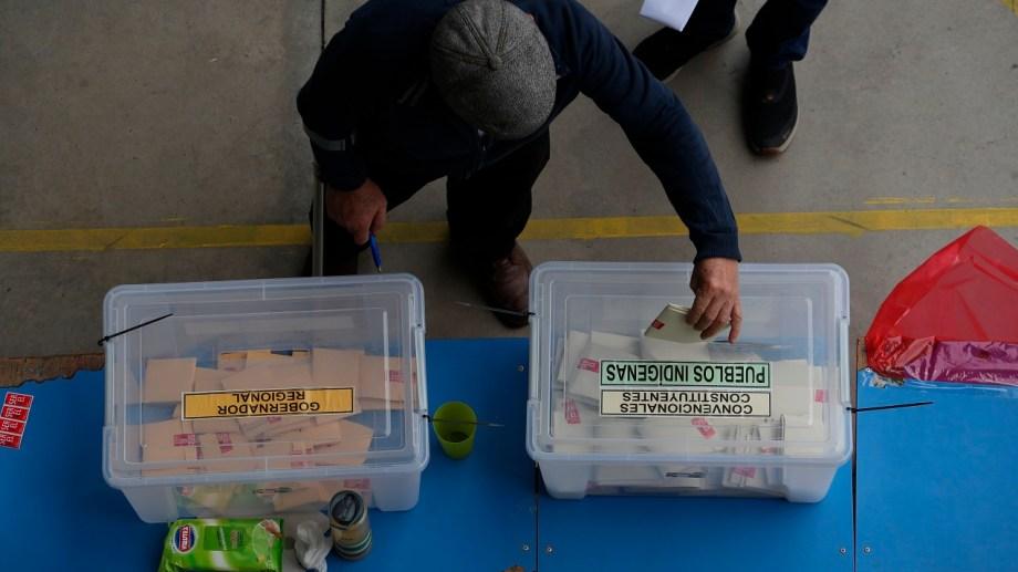 Un elector deposita su voto en la urna con el cupo para pueblos indígenas (AP Photo/Esteban Felix)