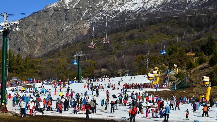 En la base del cerro Catedral, la nieve es artificial y ayer muchos turistas disfrutaban el sector de la base. Arriba, pocos registros. Foto: Alfredo Leiva