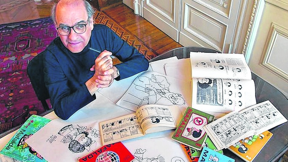 Quino nos mira desde algún lugar con Mafalda sobre la mesa.