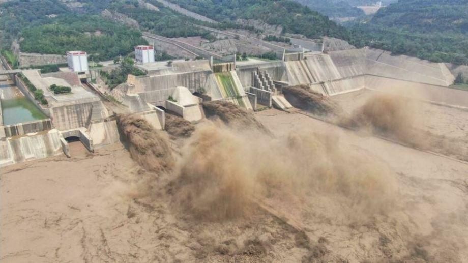 Esta foto aérea tomada el 5 de julio de 2021 muestra el agua que se libera de la presa del embalse Xiaolangdi en Luoyang, en la provincia central china de Henan, que ha sido golpeada por tormentas severas y lluvias torrenciales (Foto AFP)