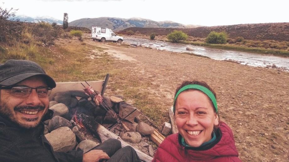 """Pablo y Karen y un asadito en el río Centinela, cerca de El Calafate, Santa Cruz. Detrás, la ambulancia que transformaron en un camper para viajar y vivir a bordo. Los amigos la bautizaron """"La Moscovita""""."""