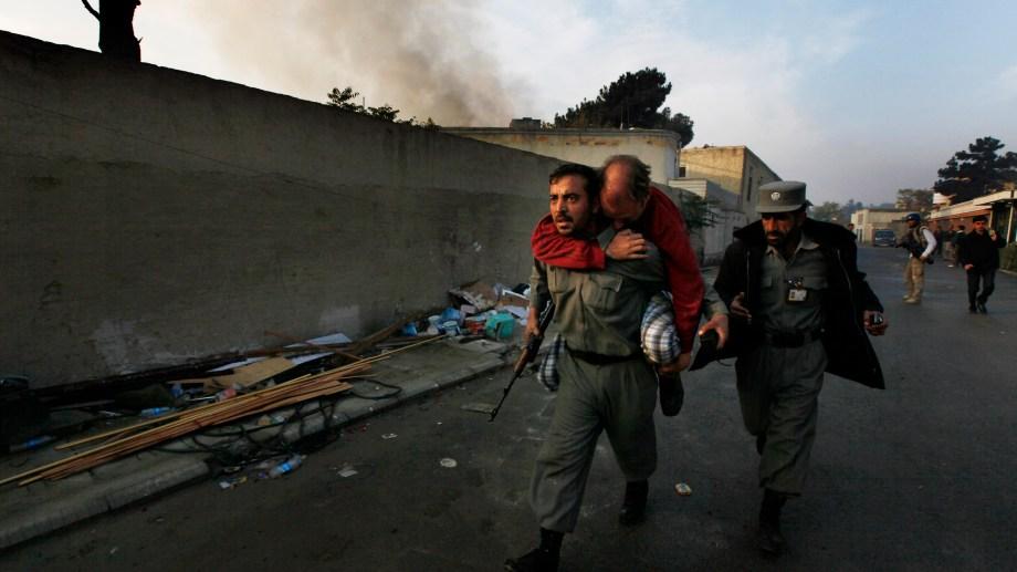 Un policía afgano transporta a un  herido durante uan escaramuza en Kabul