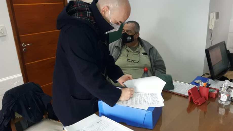 El secretario de la Legislatura, Alejandro Cortes firma la cesión de los lotes. Gatica recuperó la conducción de APEL y, ahora, el manejo de los lotes de la causa, que derivó en su condena penal. Foto: Gentileza.