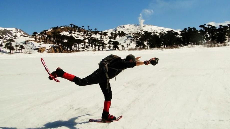 Flavio con sus raquetas de nieve sobre la laguna Escondida congelada por completo en Caviahue Copahue, con las araucarias y la fumarola del volcán de fondo en la cordillera neuquina. Foto: De la Patagonia al Mundo.
