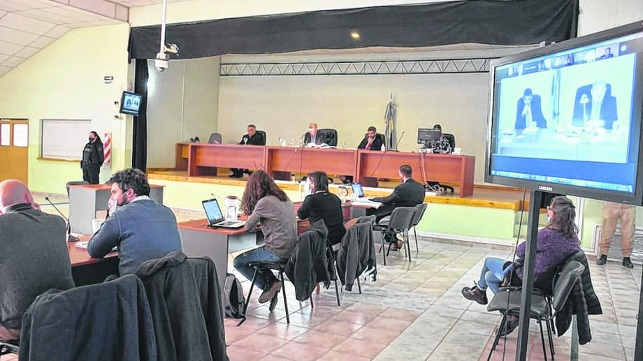 El tribunal en la sala de audiencias. La fiscalía y las querellas concurren al salón de AMUC. Las defensas están de forma virtual. Foto Yamil Regules.