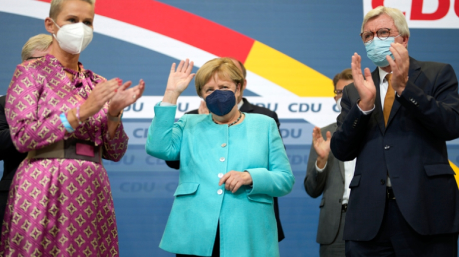 German Chancellor Angela Merkel waves as leading CDU members applaud after the German parliament elections at the Christian Democratic Union, CDU, party's headquarters in Berlin, Sunday, Sept. 26, 2021. German voters are choosing a new parliament in an election that will determine who succeeds Chancellor Angela Merkel after her 16 years at the helm of Europe's biggest economy.(AP Photo/Markus Schreiber)