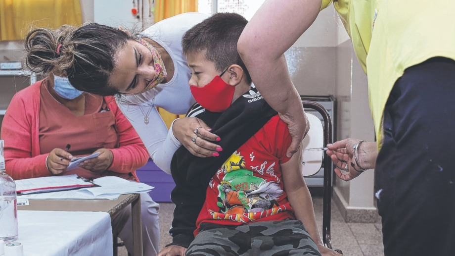 """""""Sí que duele má"""". Toda la contención posible se desplegó en las salitas de vacunación en las escuelas de Roca.  Foto Juan Thomes"""